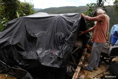 Moises Perez looks at some of his belongings covered by a tarpaulin, outside his home after Hurricane Maria hit the island in September 2017, in Naguabo, Puerto Rico, Jan. 26, 2018.