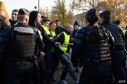 """French gendarmes face """"Yellow Vest"""" protesters demonstrating on the Champs-Elysees, in Paris, France, Nov. 17, 2018,"""