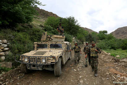 """FILE - Afghan Special Forces patrol at the site where a MOAB, or ''mother of all bombs,"""" was dropped on the Achin district of the eastern province of Nangarhar, Afghanistan, April 23, 2017."""