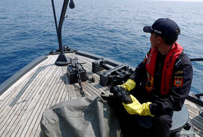 FILE - Indonesian customs officers patrol at a search area for Lion Air flight JT610 in Karawang waters, Indonesia, Nov. 1, 2018.