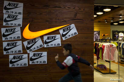 A child runs past protest signs pasted around a Nike logo in support of the strike by workers of Yue Yuen Industrial Holdings in Dongguan, during an International Labour Day rally in Hong Kong May 1, 2014.