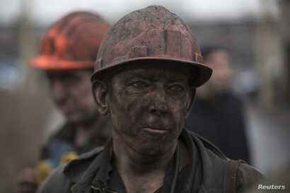 A miner waits for a bus after leaving Zasyadko coal mine in Donetsk March 4, 2015. Dozens of miners were trapped underground and feared dead after a blast on Wednesday at a coal mine in the eastern Ukrainian rebel stronghold of Donetsk, with rescuers...