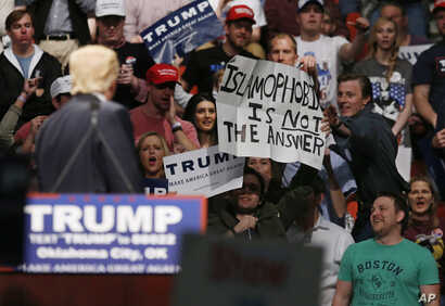 "FILE - Republican presidential candidate Donald Trump, left, looks on as one of his supporter reaches for a sign that reads ""Islamophobia is not the answer,"" at a rally in Oklahoma City, Feb. 26, 2016."