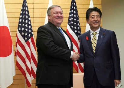 U.S. Secretary of State Mike Pompeo, left, shakes hands with Japanese Prime Minister Shinzo Abe at Abe's office in Tokyo, Oct. 6, 2018.