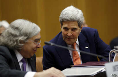 US Secretary of State John Kerry talks to US Secretary of Energy Ernest Moniz (L) during a plenary session at the United Nations building in Vienna, Austria, July 14, 2015.