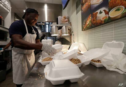Tony Mertin packages hot meals at the Chef Creole restaurant at Miami International Airport, Jan. 15, 2019, in Miami.