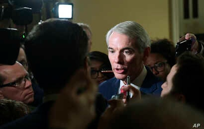 Reporters gather around Sen. Rob Portman, R-Ohio, on Capitol Hill in Washington, Dec. 15, 2017, as they ask questions on the progress of an agreement on a sweeping overhaul of the nation's tax laws.