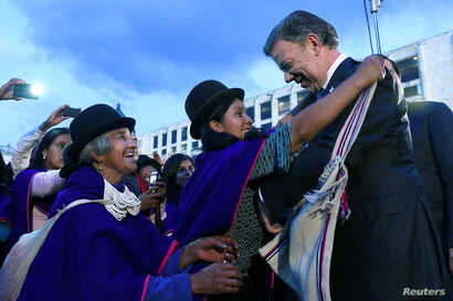 Colombia's President Juan Manuel Santos receives handicrafted presents from Misak natives in Bogota, Colombia, Oct. 10, 2016. Santos says an end to conflict with FARC would open up vast areas to development and lead to new growth of up to 1.5 percent...