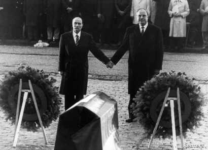 FILE - Helmut Kohl (R) stands hand in hand with former French President Francois Mitterrand (L), Sept. 22, 1984, during their visit to the former Verdun battlefields.