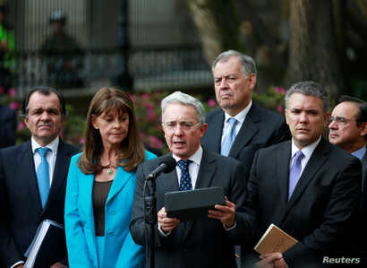 Former Colombian President Alvaro Uribe, center, accompanied by members of the Democratic Center party, speaks after a meeting with Colombian President Juan Manuel Santos at Narino Palace in Bogota, Colombia, Oct. 5, 2016.