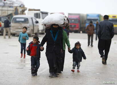 Internally displaced Syrians carry their belongings as they arrive at a refugee camp near the Bab al-Salam crossing, across from Turkey's Kilis province, on the outskirts of the northern border town of Azaz, Syria, Feb. 6, 2016.