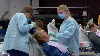 Two volunteer dentists work with a patient at the RAM Clinic, a free mobile health center set up in a school in Charleston, WV. Saturday, Oct. 20, 2018.
