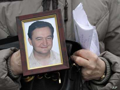 FILE - A portrait of lawyer Sergei Magnitsky, who died in jail, is held by his mother, Nataliya Magnitskaya, as she speaks during an interview with the AP in Moscow, Nov. 30, 2009.