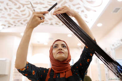 Huda Quhshi, owner and cosmetologist at the Le'Jemalik Salon and Boutique, cuts the hair of a customer ahead of the Eid al-Fitr Islamic holiday in Brooklyn, New York, June 21, 2017.
