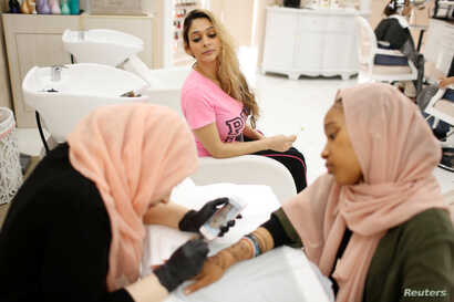 Farah Ibrahim, 25, center, watches as henna is applied on the hands of a customer ahead of the Eid al-Fitr Islamic holiday at the Le'Jemalik Salon and Boutique in Brooklyn, New York, June 21, 2017.