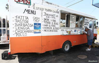 "A voter registration sign is seen on a taco truck, as part of the U.S. Hispanic Chamber of Commerce's ""Guac the Vote"" campaign, in Houston, Texas, Sept. 29, 2016."