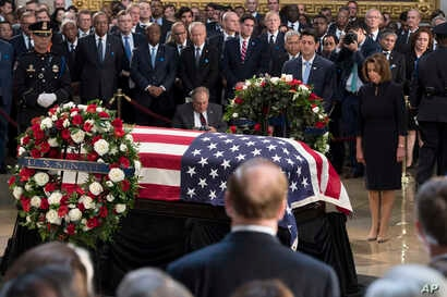 Speaker of the House Paul Ryan, center, and House minority leader Nancy Pelosi, right, pay their respects before the flag-draped coffin holding the remains of Sen. John McCain, Aug. 31, 2018, at the U.S. Capitol in Washington.