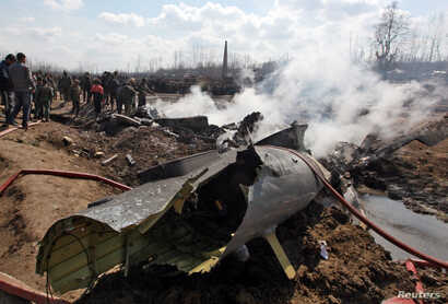 People stand next to the wreckage of Indian Air Force's helicopter after it crashed in Budgam district in Kashmir Feb. 27, 2019.