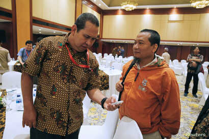 Former Indonesian militant Toni Togar, right, talks with Sarinah Jakarta bomb victim Denny Mahieu during a meeting between former militants and victims in Jakarta, Indonesia, Feb. 28, 2018.