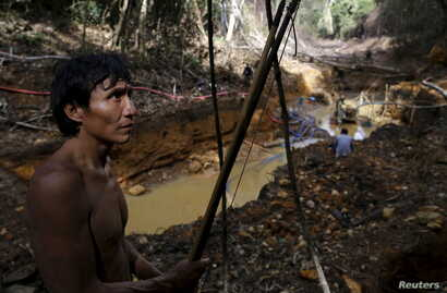 An Yanomami indian stands near an illegal gold mine during Brazil's environmental agency operation against illegal gold mining on indigenous land, in the heart of the Amazon rainforest, in Roraima state, Brazil, April 17, 2016.