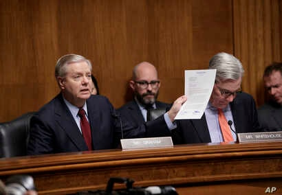 Sen. Lindsey Graham, chairman of the Senate Judiciary subcommittee on Crime and Terrorism, joined by Sen. Sheldon Whitehouse, displays a letter to FBI Director James Comey saying Congress needs to get to the bottom of charges by President Trump that ...