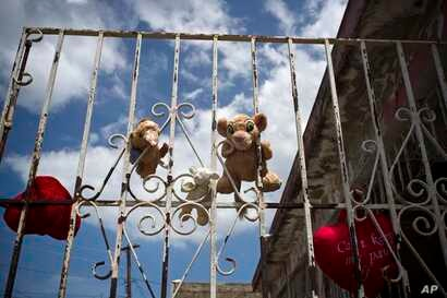 Plush toys, recovered from a flooded home, hang out to dry on a wrought iron gate in the community of Ingenio in Toa Baja, Puerto Rico, Oct. 2, 2017.