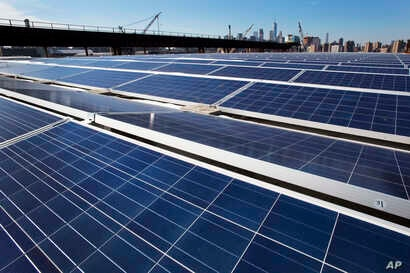 FILE - A rooftop is covered with solar panels at the Brooklyn Navy Yard in New York, Feb. 14, 2017.