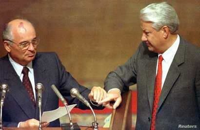 Then Russian President Boris Yeltsin and then Soviet President Mikhail Gorbachev touch hands during Gorbachev's address to the Extraordinary meeting of the Supreme Soviet of Russian Federation in Moscow, August 23, 1991.