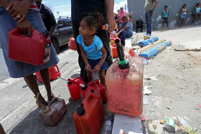 Abi de la Paz de la Cruz, 3, holds a gas can as she waits in line with her family, to get fuel from a gas station, in the aftermath of Hurricane Maria, in San Juan, Puerto Rico, Sept. 25, 2017.
