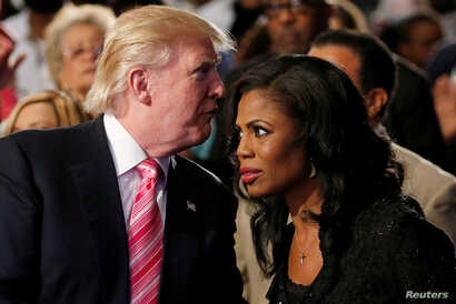 FILE - Republican presidential nominee Donald Trump and Omarosa Manigault attend a church service in Detroit, Michigan, Sept. 3 2016.