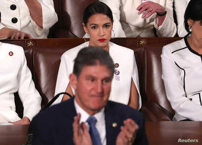 Rep. Alexandria Ocasio-Cortez (D-NY) (R) remains in her seat as Senator Joe Manchin (D-WV) stands and applauds as U.S. President Donald Trump delivers his second State of the Union address to a joint session of Congress at the U.S. Capitol in Washing...
