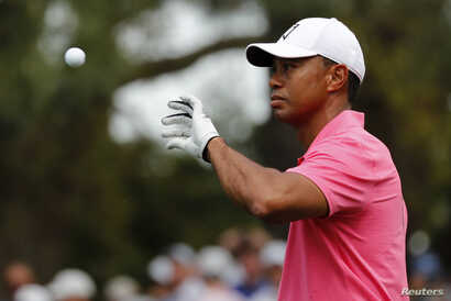 Tiger Woods of the U.S. catches a ball from his caddie on the first hole during practice for the 2018 Masters golf tournament at Augusta National Golf Club in Augusta, Georgia, April 2, 2018.