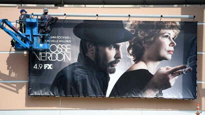 """Workers put up a poster for the upcoming FX limited series """"Fosse/Verdon"""" near the entrance to Fox Studios, March 19, 2019, in Los Angeles."""