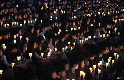 High school students hold candles to pay their respects to the victims of the sunken ferry Sewol during a ceremony on the eve of the second anniversary of the ferry sinking in Ansan, South Korea, April 15, 2016.