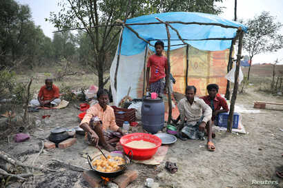 FILE - A man cooks a meal in his makeshift restaurant on the island of Bhasan Char in the Bay of Bengal, Bangladesh, Feb. 14, 2018.