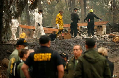 Investigators recover human remains at a home burned in the Camp Fire, Nov. 15, 2018, in Magalia, Calif. Many of the missing in the deadly Northern California wildfire are elderly residents in Magalia, a forested town of about 11,000 north of the des...