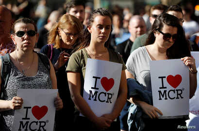 Women wait to take part in a vigil for the victims of an attack on concert goers at Manchester Arena, in central Manchester, Britain, May 23, 2017.