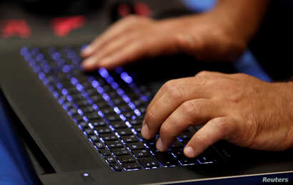 FILE - A man types into a keyboard during the Def Con hacker convention in Las Vegas, Nevada, on July 29, 2017.