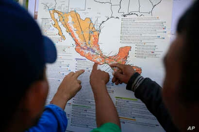 Migrants discuss their journey using a map posted inside the sports complex where thousands of migrants have been camped out for several days in Mexico City, Nov. 9, 2018.
