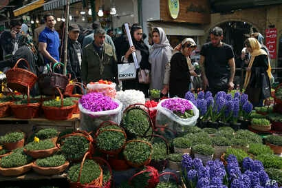 Iranians shop for hyacinths, garlic, sprouts and other items used to celebrate the Iranian New Year, ahead of the holiday, at the Tajrish traditional bazaar in northern Tehran, March 19, 2018.