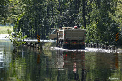 Members of the 1st Combat Engineer Company of the U.S. National Guard of Laurinburg, North Carolina, navigate flood waters in the aftermath of Hurricane Florence, now downgraded to a tropical depression, in Whiteville, North Carolina, Sept. 18, 2018....