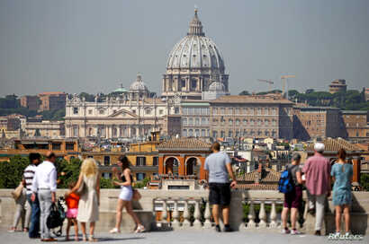 FILE - Tourists take pictures of Saint Peter's Basilica from Pincio terrace in downtown Rome, Italy, Aug. 3, 2017.