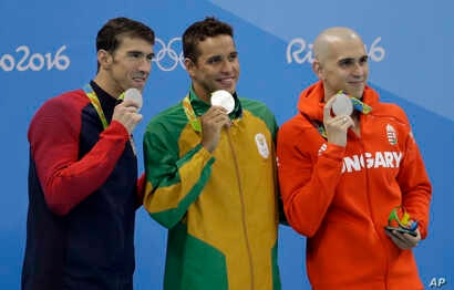 Men's 100-meter butterfly silver medalists, from left, United States' Michael Phelps, South Africa's Chad Le Clos and Hungary's Laszlo Cseh hold up their medals at the medal ceremony during swimming competitions at the 2016 Summer Olympics, Friday, A...