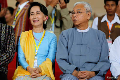 FILE - Myanmar State Counsellor Aung San Suu Kyi and Myanmar's president Htin Kyaw attend a photo opportunity after the opening ceremony of the 21st Century Panglong Conference in Naypyitaw, Myanmar, May 24, 2017.