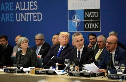 From left, British Prime Minister Theresa May, U.S. President Donald Trump and NATO Secretary General Jens Stoltenberg listen to Belgian Prime Minister Charles Michel as he speaks during a working dinner meeting at the NATO headquarters during a NATO...