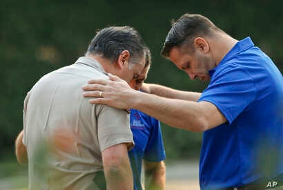 Ventura County Sheriff's Office Capt. Garo Kuredjian, left, embraces chaplains with the Billy Graham Rapid Response Team as they pray near the site of Wednesday's mass shooting in Thousand Oaks, Calif., Nov. 9, 2018. Investigators continue to work to...