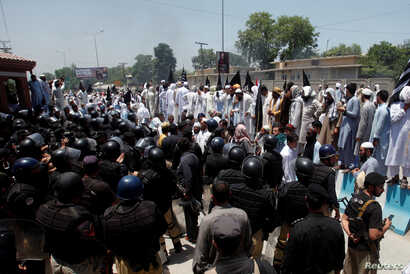 Police officers stand guard at the assembly building during a demonstration against the constitutional amendment bill for the merger of Federally Administered Tribal Areas (FATA) with Khyber Pakhtunkhwa (KPK) province, in Peshawar, Pakistan, May 27, ...