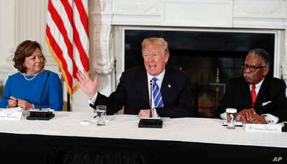 President Donald Trump joined by New Mexico Gov. Susana Martinez, left, and Vicksburg, Miss., Mayor George Flaggs, Jr., right, speaks in the State Dining Room of the White House, Feb. 12, 2018, during a meeting with state and local officials about in...