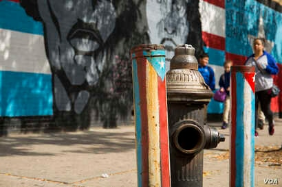 A mural and painted pipes in the colors of Puerto Rico's and Cuba's flags brighten the streets of East Harlem, New York, home to one of the largest Puerto Rican diaspora communities in the U.S. (R. Taylor/VOA)