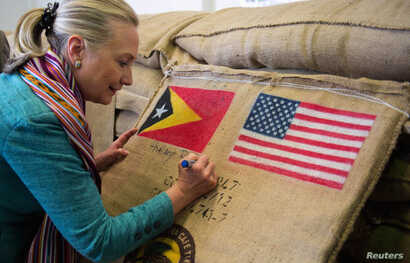 U.S. Secretary of State Hillary Clinton (C) autographs a sack of coffee beans with the flags of East Timor and the U.S. , at the Timor Coffee Cooperative in Dili September 6, 2012.